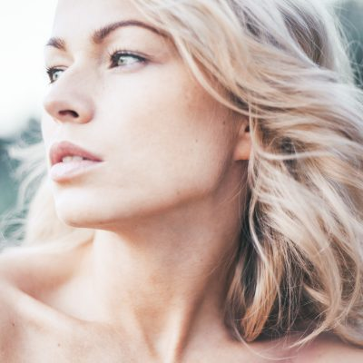 Beautiful young blond woman outdoors. Sunny day. Nature summer background. Outside close-up portrait of beautiful young happy woman with fresh and clean skin