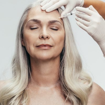 Doctor with gloves injecting a botox with an needle into temple of the senior woman against grey background. Woman getting anti aging injection on her face to reduce wrinkles.